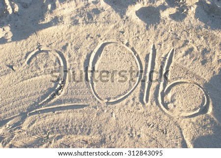 2016 writing in the sand at the beach. - stock photo