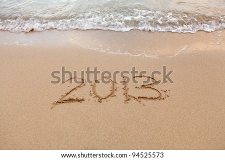 2013 written in sand on beach with sea waves starting to erase the word - stock photo