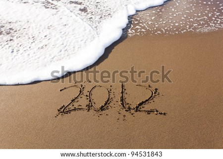 2012 written in sand on beach with sea waves starting to erase the word - stock photo