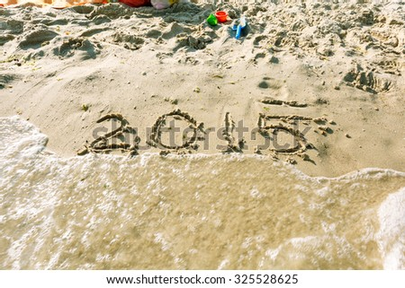 2015 written in sand, on tropical beach