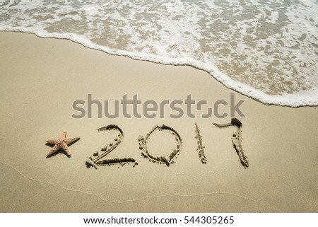2017 written in sand write on tropical beach