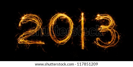 2013 written in sparklers isolated on black - stock photo
