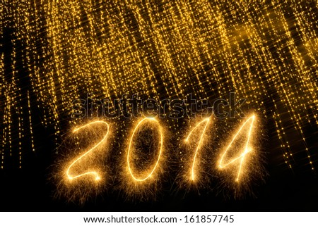 2014 written in sparkling letters under a curtain of sparks - stock photo