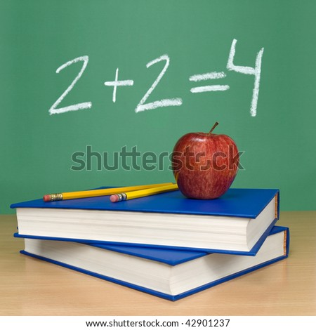 2 + 2 = 4 written on a chalkboard. Books, pencils and an apple on the foreground. - stock photo