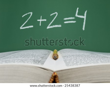 2 + 2 = 4 written on a chalkboard with an open book and a pencil on foreground.