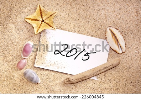2015, written on a note in the sand with seashells - stock photo