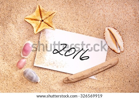 2016, written on a note in the sand with seashells - stock photo