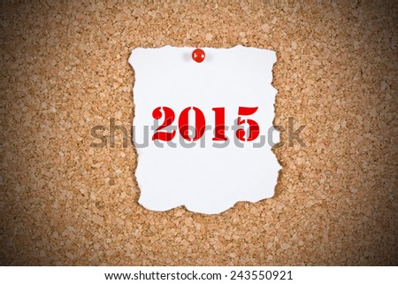 2015 written on a sheet with ragged edges mounted on cork billboard - stock photo