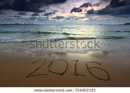 2016 written on sand during amazing sunset. Nature composition