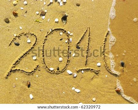 2010 written on the beach and one wavelet erasing it - stock photo