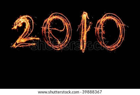 2010 written with sparklers in one line on a black background - stock photo
