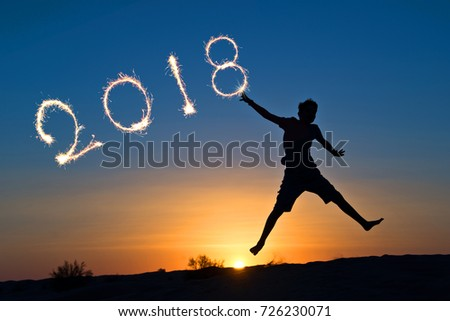 2018 written with sparkles, silhouette of a boy jumping in the sun