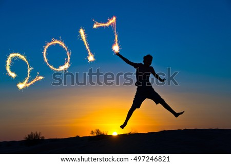 2017 written with sparkles, silhouette of a boy jumping in the sun, 2017 new year concept
