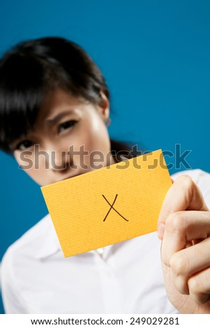 """Wrong"" on business card holding by Asian businesswoman on studio blue background. - stock photo"