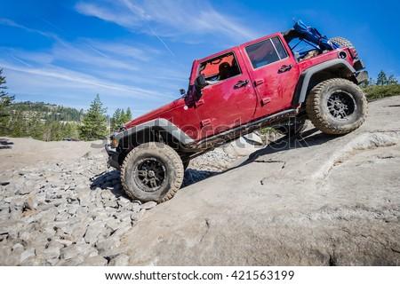 4x4 truck descending steep rock on the Rubicon Trail near Lake Tahoe, CA. - stock photo