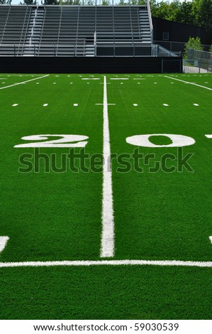 20 Yard Line on American Football Field with Bleachers - stock photo