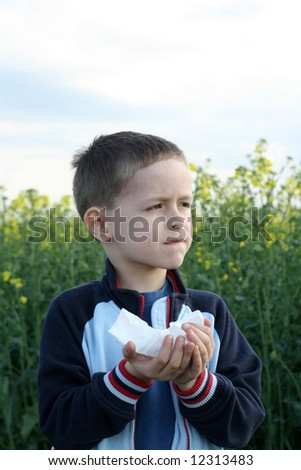6 yars old boy with tissue on the field of flowers - stock photo