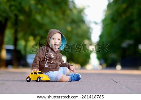 1 year baby sitting on the sidewalk in a brown jacket with a hood with white print in blue shorts and blue sneakers, plays a yellow toy car on a background of green trees and the city.  - stock photo