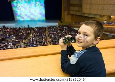 9-year boy with binoculars in a theater amphitheatre - stock photo