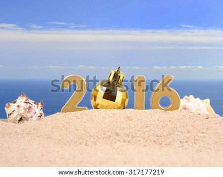 2016 year golden figuresl on a beach sand against the background of the sea