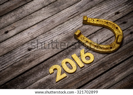 2016 year golden number and horseshoe on wooden background - stock photo
