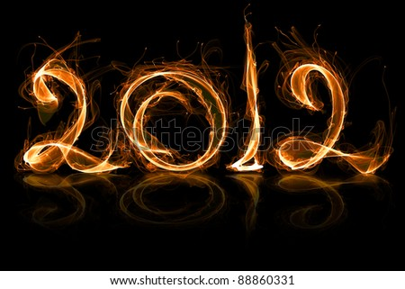 2012 year in fire with sparkles on black - stock photo