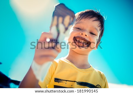 3 year old asian caucasian boy enjoying a melting chocolate ice-cream on a sweltering hot summer day. Clear blue summer sky in background - stock photo