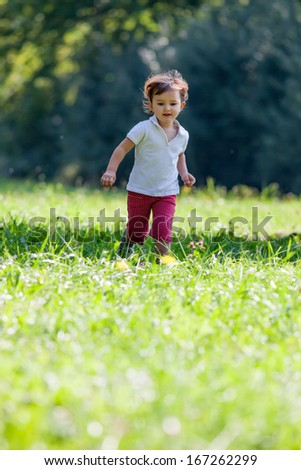 2 year-old baby running in a park