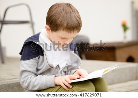 7 year old boy, a student reading a book on the terrace in the garden - stock photo