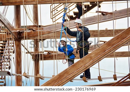 7 year old boy and his father enjoying a challenging rope course sky trail in the Andorra Pyrenees Mountains - stock photo