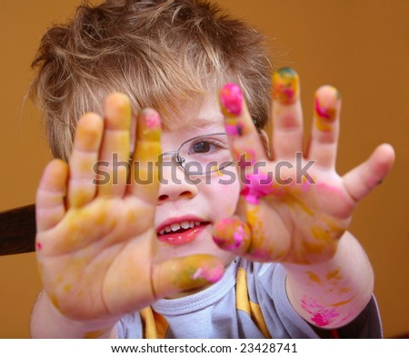 4 year old boy covered in bright paint. - stock photo
