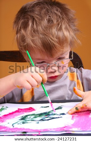 4 year old boy covered in bright paint - stock photo