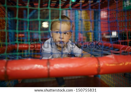 3 year old boy having fun on the playground inside trade center