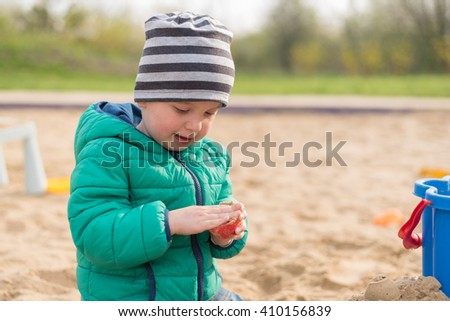 2 year old boy having fun outdoors in sandpit on playground - stock photo