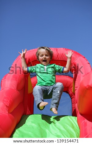 3 year old boy jumping down the slide on an inflatable bouncy castle - stock photo