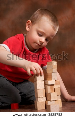 4 year old boy playing with wooden blocks - stock photo