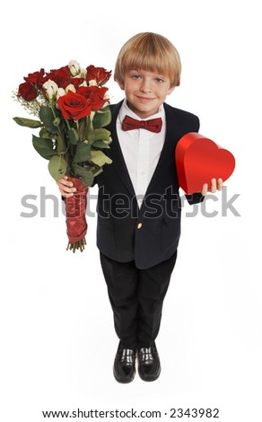 8-year-old boy presenting a heart shaped box of chocolates and a bouquet of roses, wearing a suite and red bowtie on a white background