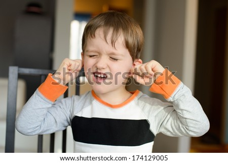 4 year old boy screaming and clog his ears with fingers at home - stock photo