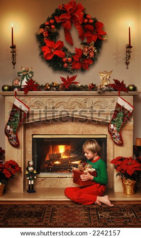 8 year old boy sitting beside the fire with a wrapped Christmas gift in his lap - stock photo