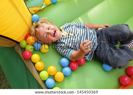 2 year old boy smiling on an inflatable bouncy castle - stock photo