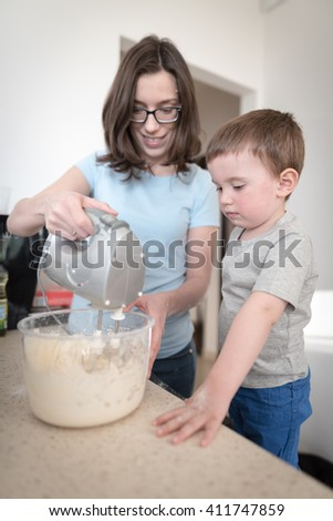 2 year old boy standing on chair in kitchen with his mother and preparing dough for chocolate chip cookies with food processor  - stock photo