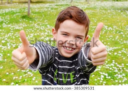 7 year old boy with his thumbs up - stock photo