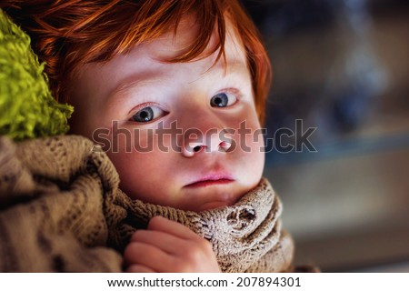 4 year old boy wrapped in his security blanket, lying on a fuzzy green pillow -- image taken in Reno, Nevada, USA - stock photo