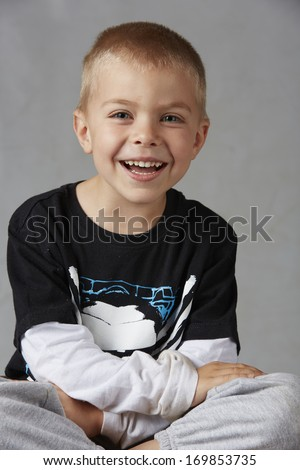 5 year old caucasian boy with short blonde hair, blue eyes and a light, healthy complexion wearing a long sleeve t-shirt. Shot in studio on a grey background.