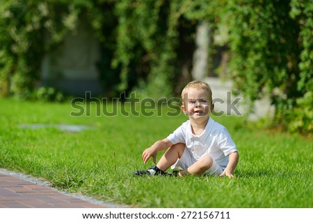 2 year old child in the park, in white shorts and a white T-shirt. Blond boy with blue eyes. Cheerful child in the summer park. Laughing baby in nature. - stock photo