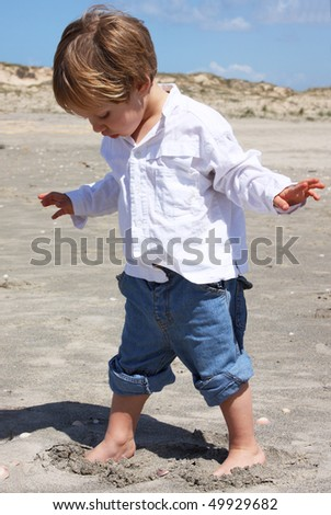 2-year-old child playing on the beach - stock photo