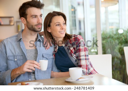 30-year-old couple sitting in coffee shop - stock photo