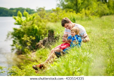 2-3-year-old cute boy with his father are sitting on the river side. - stock photo