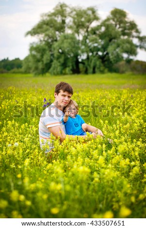 2-3-year-old cute boy with his father on the field with yellow flowers. - stock photo