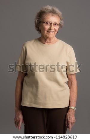 80 Year Old Elderly Senior Happy Portrait Standing on Gray Background - stock photo